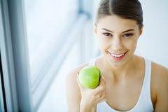 Χαμογελώντας γυναίκα με το όμορφο χαμόγελο, λευκιά εκμετάλλευση Apple δοντιών Χ Στοκ Φωτογραφία