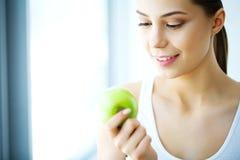 Χαμογελώντας γυναίκα με το όμορφο χαμόγελο, λευκιά εκμετάλλευση Apple δοντιών Χ Στοκ εικόνα με δικαίωμα ελεύθερης χρήσης