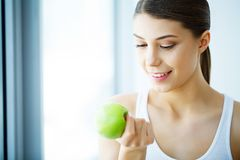 Χαμογελώντας γυναίκα με το όμορφο χαμόγελο, λευκιά εκμετάλλευση Apple δοντιών Χ Στοκ φωτογραφίες με δικαίωμα ελεύθερης χρήσης