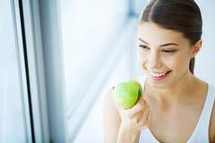 Χαμογελώντας γυναίκα με το όμορφο χαμόγελο, λευκιά εκμετάλλευση Apple δοντιών Χ Στοκ εικόνες με δικαίωμα ελεύθερης χρήσης