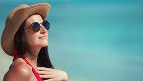 Χαμογελώντας γυναίκα μόδας ταξιδιού στα γυαλιά ηλίου καπέλων που κάνουν ηλιοθεραπεία απολαμβάνοντας τη θέα θάλασσας που έχει τη θ φιλμ μικρού μήκους