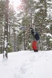 Χαμογελώντας γυναίκα που αναρριχείται επάνω στο λόφο μέσω snowdrifts Στοκ Εικόνα
