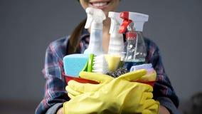Χαμογελώντας γυναίκα που ανυψώνει επάνω τον κάδο με τις πολυάριθμες οικιακές καθαρίζοντας ουσίες στοκ φωτογραφίες