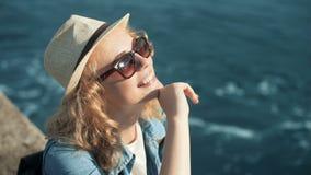 Χαμογελώντας γυναίκα που απολαμβάνει το θερινό ήλιο σε ένα άσπρο καπέλο ήλιων στην παραλία απόθεμα βίντεο