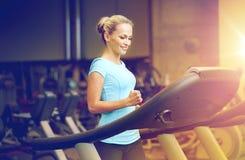 Χαμογελώντας γυναίκα που ασκεί treadmill στη γυμναστική στοκ εικόνες