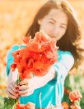 Χαμογελώντας γυναίκα που δίνει μια ανθοδέσμη των παπαρουνών στοκ εικόνες με δικαίωμα ελεύθερης χρήσης