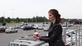 Χαμογελώντας γυναίκα που εξετάζει έναν χώρο στάθμευσης αυτοκινήτων κρατώντας ένα ποτήρι του καφέ για να πάρει μαζί φιλμ μικρού μήκους