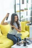 χαμογελώντας γυναίκα που εφαρμόζει τον ψεκασμό τρίχας στην αποτύπωση hairstyle καθμένος στον καναπέ στοκ εικόνες με δικαίωμα ελεύθερης χρήσης