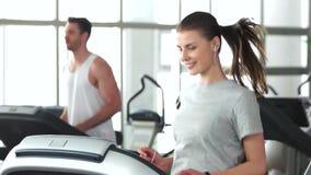 Χαμογελώντας γυναίκα που κάνει την καρδιο άσκηση στη γυμναστική φιλμ μικρού μήκους
