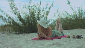 Χαμογελώντας γυναίκα που κουβεντιάζει on-line στο κινητό τηλέφωνο στην παραλία απόθεμα βίντεο