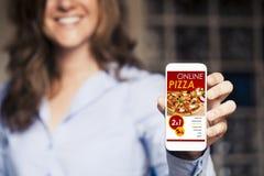 Χαμογελώντας γυναίκα που κρατά ένα κινητό τηλέφωνο με τις αγορές app πιτσών στην οθόνη Στοκ φωτογραφία με δικαίωμα ελεύθερης χρήσης