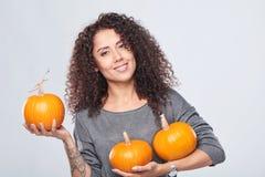 Χαμογελώντας γυναίκα που κρατά τις ώριμες κολοκύθες στοκ φωτογραφία με δικαίωμα ελεύθερης χρήσης