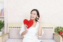 Χαμογελώντας γυναίκα που κρατά το κόκκινο σύμβολο αγάπης καρδιών Στοκ εικόνες με δικαίωμα ελεύθερης χρήσης