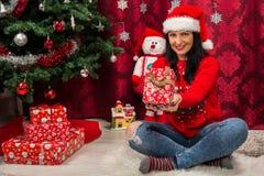 Χαμογελώντας γυναίκα που παρουσιάζει δώρο Χριστουγέννων στοκ φωτογραφία