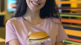 Χαμογελώντας γυναίκα που παρουσιάζει πριν από νόστιμο και αρωματικό burger καμερών, κίνδυνος παχυσαρκίας απόθεμα βίντεο