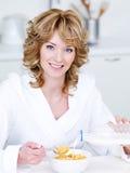 Χαμογελώντας γυναίκα που τρώει τις νιφάδες καλαμποκιού Στοκ φωτογραφία με δικαίωμα ελεύθερης χρήσης