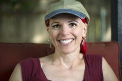 Χαμογελώντας γυναίκα που φορά τη σφαίρα ΚΑΠ στοκ φωτογραφία