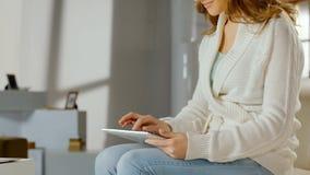 Χαμογελώντας γυναίκα που χρησιμοποιεί app στο PC ταμπλετών στο σπίτι, κουβεντιάζοντας on-line, κινηματογράφοι προσοχής Στοκ Εικόνες