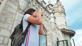 Χαμογελώντας γυναίκα σακιδίων πλάτης που απολαμβάνει την αρχαία αρχιτεκτονική που κάνει τη φωτογραφία του μεσαιωνικού κάστρου απόθεμα βίντεο