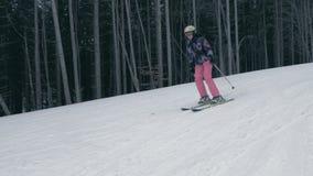 Χαμογελώντας γυναίκα στα ροδοειδή εσώρουχα που κάνει σκι γρήγορα Carpathians το χειμώνα στην slo-Mo απόθεμα βίντεο