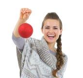 Χαμογελώντας γυναίκα στη σφαίρα Χριστουγέννων εκμετάλλευσης πουλόβερ Στοκ Εικόνες