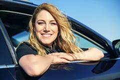 Χαμογελώντας γυναίκα στο αυτοκίνητο μια θερινή ημέρα Στοκ Φωτογραφία
