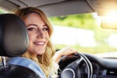 Χαμογελώντας γυναίκα στο αυτοκίνητο μια θερινή ημέρα Στοκ Εικόνες