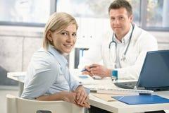 Χαμογελώντας γυναίκα στο γραφείο του γιατρού Στοκ εικόνες με δικαίωμα ελεύθερης χρήσης