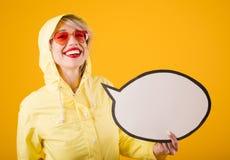 Χαμογελώντας γυναίκα στο κίτρινο αδιάβροχο Το αστείο κορίτσι στο κίτρινο λεκτικό buble κενό copyspace εκμετάλλευσης υποβάθρου εσε Στοκ Εικόνες
