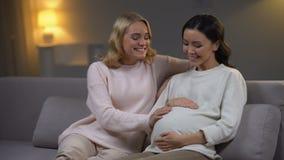 Χαμογελώντας γυναίκα σχετικά με tummy του ευτυχούς έγκυου φίλου της, μητρότητα, οικογένεια φιλμ μικρού μήκους
