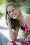 Χαμογελώντας γυναίκα υπαίθρια με το τηλέφωνο κυττάρων στοκ φωτογραφία με δικαίωμα ελεύθερης χρήσης