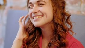 Χαμογελώντας γυναίκα Flirty που παίζει τη σγουρή τρίχα πιπεροριζών φιλμ μικρού μήκους