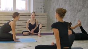 Χαμογελώντας γυναίκες ομάδας πρίν εκπαιδεύει την ομιλία και το τέντωμα στην κατηγορία γιόγκας Στοκ εικόνες με δικαίωμα ελεύθερης χρήσης