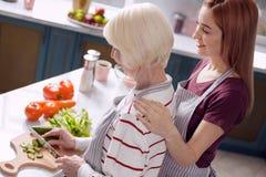 Χαμογελώντας γυναίκες που συνδέουν μαγειρεύοντας το γεύμα από κοινού Στοκ Φωτογραφία