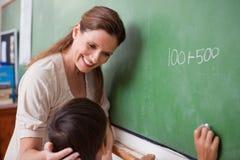 Χαμογελώντας δάσκαλος που βοηθά schoolboy Στοκ Εικόνα