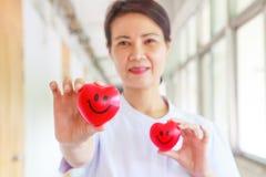 Χαμογελώντας δύο κόκκινες καρδιές που κρατιούνται με το χαμόγελο των θηλυκών χεριών νοσοκόμων ` s, που αντιπροσωπεύουν δίνοντας τ Στοκ εικόνα με δικαίωμα ελεύθερης χρήσης