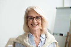 Χαμογελώντας ελκυστική ανώτερη επιχειρηματίας που φορά το επικεφαλής sho γυαλιών στοκ φωτογραφίες