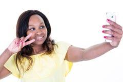 Χαμογελώντας ελκυστική αφρικανική γυναίκα που παίρνει μια νίκη Β δάχτυλων selfie χειρονομία στοκ εικόνες