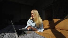 Χαμογελώντας ελκυστική γυναίκα που βρίσκεται στο κρεβάτι που χρησιμοποιεί το lap-top απόθεμα βίντεο