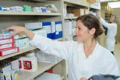 Χαμογελώντας ελκυστικός νέος θηλυκός φαρμακοποιός στο φαρμακείο στοκ φωτογραφίες με δικαίωμα ελεύθερης χρήσης