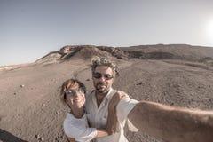 Χαμογελώντας ενήλικο ζεύγος που παίρνει selfie στο εθνικό πάρκο Namib Naukluft, προορισμός ταξιδιού στη Ναμίμπια, Αφρική Fisheye, στοκ φωτογραφία