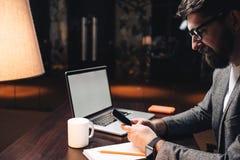 Χαμογελώντας επιχειρηματίας με το lap-top και smartwatch τη χρησιμοποίηση του coworking στούντιο σοφιτών smartphone τη νύχτα Ο γε Στοκ φωτογραφία με δικαίωμα ελεύθερης χρήσης