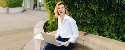 Χαμογελώντας επιχειρηματίας που εργάζεται με το lap-top και τα έγγραφα σε υπαίθριο στοκ φωτογραφία με δικαίωμα ελεύθερης χρήσης