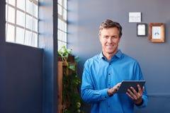 Χαμογελώντας επιχειρηματίας που στέκεται σε ένα γραφείο που χρησιμοποιεί μια ψηφιακή ταμπλέτα Στοκ Εικόνες