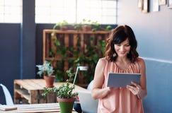 Χαμογελώντας επιχειρηματίας που στέκεται σε ένα γραφείο που χρησιμοποιεί μια ψηφιακή ταμπλέτα Στοκ φωτογραφία με δικαίωμα ελεύθερης χρήσης