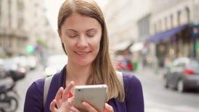 Χαμογελώντας επιχειρηματίας που στέκεται στην οδό που χρησιμοποιεί το smartphone Επαγγελματικές θηλυκές ειδήσεις ανάγνωσης ξεφυλλ φιλμ μικρού μήκους