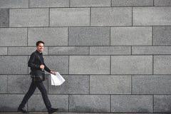 Χαμογελώντας επιχειρηματίας που τρέχει γρήγορα με το χαρτοφύλακα στην πόλη στοκ εικόνα