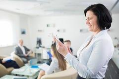 Χαμογελώντας επιχειρηματίας που χρησιμοποιεί το smartphone στην αρχή Στοκ Εικόνες