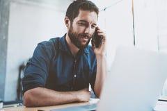 Χαμογελώντας επιχειρηματίας που χρησιμοποιεί το smartphone στο γραφείο και την παραγωγή των σημειώσεων ανασκόπηση που θολώνεται ο Στοκ φωτογραφία με δικαίωμα ελεύθερης χρήσης