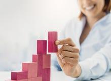 Χαμογελώντας επιχειρηματίας που χτίζει ένα επιτυχές οικονομικό διάγραμμα στοκ φωτογραφία